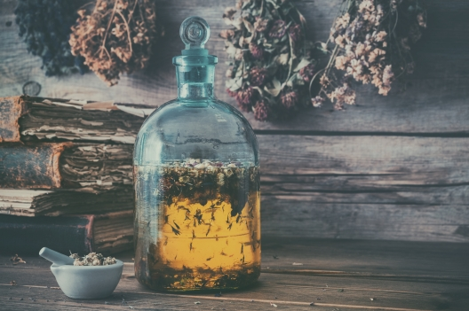 Tincture or potion bottle, old books, mortar and hanging bunches